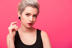 Hipster girl with blond hair and piercing over pink background. Close-up of Hipster girl with short blond hair, piercing and ear tunnels over pink color royalty free stock image