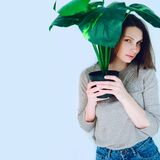 Hipster girl in blue jeans with a flower pot in hand on a white background
