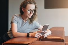 Hipster girl chatting,blogging,checking email.Student learning, studying.Online marketing,education,e-commerce,social. Young businesswoman in glasses sits on royalty free stock images