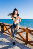Hipster girl chatting on smart phone resting at seashore Royalty Free Stock Photo