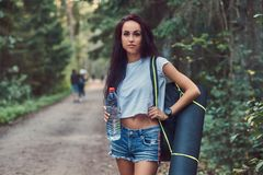 Hipster girl dressed in a shirt and shorts with tourist mat and backpack holds a bottle of water and looking at camera. Girl dressed in a shirt and shorts with royalty free stock photo