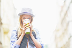 Hipster girl drinking hot beverage on city street Royalty Free Stock Image