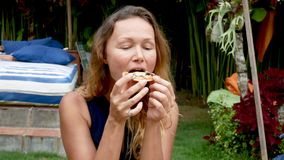 Hipster girl eating pizza and smiling to the camera in the restaurant stock footage