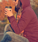 Hipster girl enjoying coffee in park Stock Image