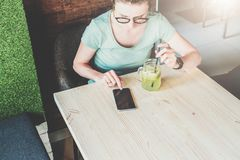 Hipster girl in eyeglasses is sitting at table, drinking beverage, using phone and looking on screen of smartphone. View from above.Hipster girl in eyeglasses Royalty Free Stock Images