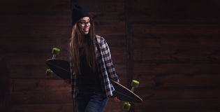 Hipster girl in glasses with a longboard Stock Photo