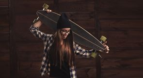 Hipster girl in glasses and with a longboard Royalty Free Stock Images