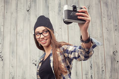 Hipster girl in glasses making selfie Stock Image