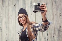 Hipster girl in glasses making selfie Stock Image