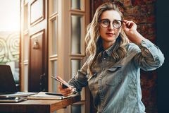Hipster girl in glasses sits in cafe at table in front of laptop,holding smartphone.Girl looking for friends in cafe. royalty free stock photography