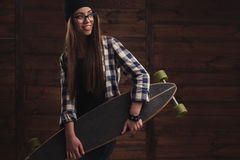 Hipster girl in glasses and with skateboard Royalty Free Stock Photo