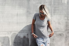 Hipster girl in gray t-shirt over street wall Royalty Free Stock Images