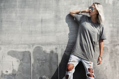 Hipster girl in gray t-shirt over street wall Stock Photography
