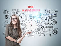 Hipster girl in green and time management toned. Hipster young girl wearing a green shirt and glasses is smiling near a gray wall with a time management sketch Royalty Free Stock Photos