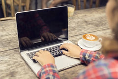 Hipster girl hands, laptop and coffee mug Royalty Free Stock Image