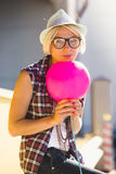 Hipster girl in hat and eyeglasses posing with pink balloon Royalty Free Stock Photos