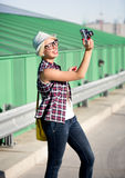 Hipster girl in hat making picture on vintage camera Royalty Free Stock Images