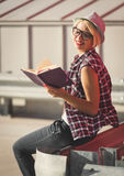 Hipster girl in hat posing with notebook on street at sunny day Stock Image