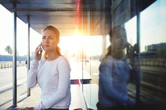 Hipster girl having cell telephone conversation with her friend which she awaits on a bus stop Royalty Free Stock Photo