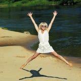 Hipster girl having fun on the beach. Near the water. Girl happily jumping on the beach. Lifestyle portrait Stock Image