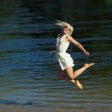 Hipster girl having fun on the beach. Near the water. Girl happily jumping on the beach. Lifestyle portrait Stock Photography