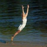 Hipster girl having fun on the beach. Near the water. Girl happily jumping on the beach. Lifestyle portrait Royalty Free Stock Photos