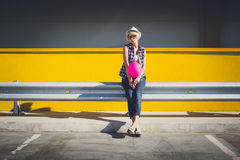 Hipster girl having fun on parking lot with pink balloon Royalty Free Stock Photography