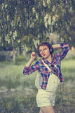 Hipster girl with headphones dancing under tree. Royalty Free Stock Photos