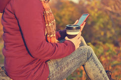 Hipster girl holding cup of coffee and phone Stock Photos