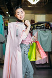Hipster girl holding dress and shopping bags in boutique, clothes shopping concept. Asian hipster girl holding dress and shopping bags in boutique, clothes Stock Image
