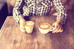 Hipster girl holding two cups of coffee on a wooden table Stock Images