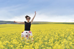 Hipster girl jumping through a canola field. Freedom concept Royalty Free Stock Image