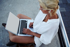Hipster girl keyboarding on portable net-book while sitting outdoors in warm summer evening Stock Photo