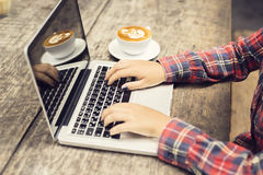 Hipster girl with laptop and cup of coffee ona wooden table Stock Photography