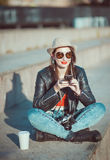 Hipster girl in leather jacket, hat with retro camera and mobile Stock Image