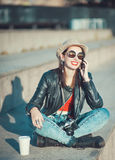 Hipster girl in leather jacket, hat with retro camera and mobile Stock Images