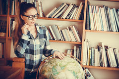 Hipster girl in library working with globe Stock Photos