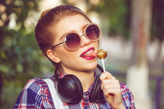 Hipster girl licking lollipop. Headphones. Royalty Free Stock Photography