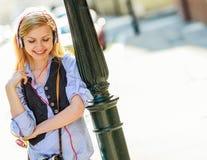 Hipster girl listening music on city street. Happy hipster girl listening music on city street Stock Image