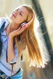 Hipster girl listening music on city street Royalty Free Stock Photography