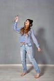 Hipster girl listening to music on headphones. Stock Photo