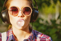 Hipster girl listening to music on headphones and chews the cud. Stock Photography