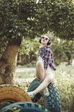 Hipster girl listening to music with headphones in summer park i Royalty Free Stock Image