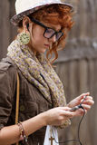 Hipster girl listening to music on mp3 player Stock Photos