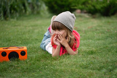 Hipster girl listens music on wireless retro looking speaker Stock Images