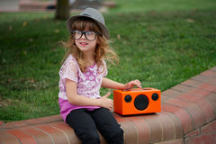 Hipster girl listens music on wireless retro looking speaker Royalty Free Stock Photo