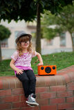 Hipster girl listens music on wireless retro looking speaker Royalty Free Stock Photography