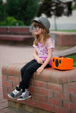 Hipster girl listens music on wireless retro looking speaker Royalty Free Stock Images