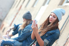 Hipster girl looking at smartphone Royalty Free Stock Photography