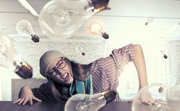Hipster girl looking from under table Royalty Free Stock Image